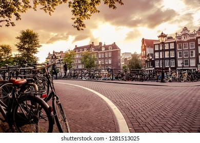 AMSTERDAM, NETHERLANDS - AUGUST 31, 2019:  Sunset seen from the city of Amsterdam with bicycles and old architecture