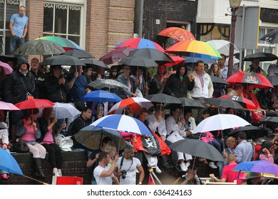 Amsterdam, Netherlands - August 7, 2010: Many people under umbrellas looking  gay parade in Amsterdam, the Netherlands.