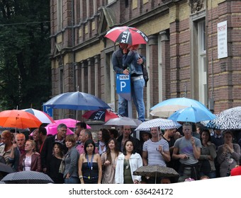 Amsterdam, Netherlands - August 7, 2010: Two people under umbrellas looking  gay parade in Amsterdam, the Netherlands.