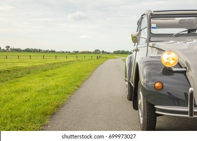 AMSTERDAM, NETHERLANDS - AUGUST 7, 2017: A French vintage classic oldtimer car Citroen 2CV Grey Charleston from 1990 in mint condition is driving through the lush green Dutch landscape