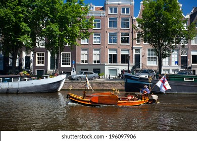 AMSTERDAM, NETHERLANDS - AUGUST 8, 2012: Elderly man enjoying a boat ride boat in a canal.