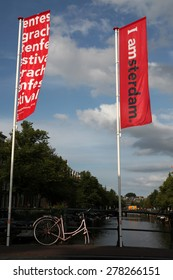 AMSTERDAM, NETHERLANDS - AUGUST 9, 2012: Old pink bicycle parked on the bridge decorated with banners with an official brand of the city in Amsterdam, Netherlands.