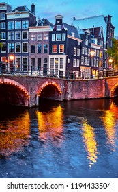 Amsterdam, Netherlands. Bridges with nighttime illumination over canals with water in Old town. Quarter with traditional dutch houses. Vertical evening landscape. Blue hour.