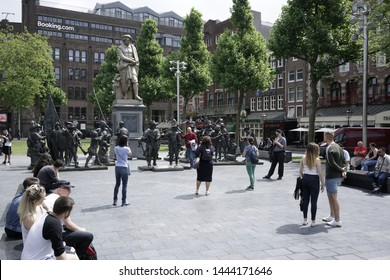 Amsterdam The Netherlands circa may 2018 sunny day on rembrandt square people taking selfiys and photos of the famous Dutch Master