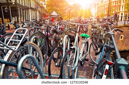 Amsterdam, Netherlands. Cycling parking along streets at channels. Sunset evening with sunshine. Bicycles is most popular transport type in Amsterdam.