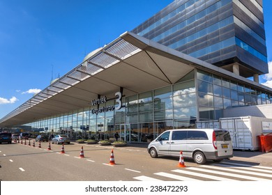 AMSTERDAM, THE NETHERLANDS - DEC 11: Airport Departures entrance with cars and taxis dropping off travellers on December 11, 2014 at the airport Schiphol of Amsterdam, the Netherlands
