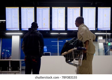 AMSTERDAM, NETHERLANDS - DEC 27, 2017: Two men are looking at the information screens to check his flight on Schiphol airport near Amsterdam