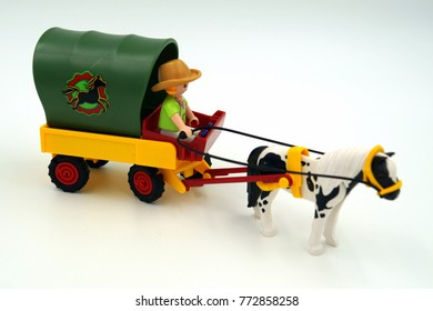 Amsterdam, The Netherlands-  December 10, 2017: Playmobil coachman traveling by covered wagon, horse-drawn Western Wagon.