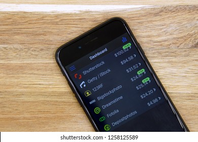 Amsterdam, the Netherlands - December 14, 2018: Black smartphone displaying Microstockr application. Microstockr is a  is a mobile app that tracks micorstock portfolio earnings.