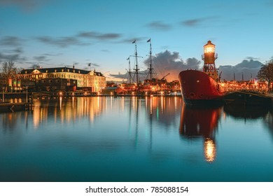 Amsterdam, Netherlands, December 16, 2017:  Lightship moored at the quay with in the background the Maritime Museum with VOC ship in Amsterdam
