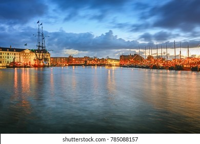 Amsterdam, Netherlands, December 16, 2017: Oosterdok canal in Amsterdam with the Maritime Museum and VOC ship on the left and historical commercial ships on the right