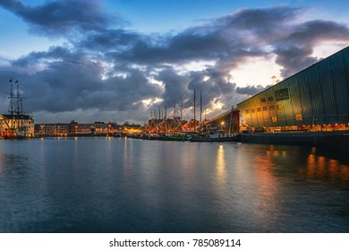 Amsterdam, Netherlands, December 16, 2017: Oosterdok canal in Amsterdam Nemo Science Museum on the right,  historical commercial ships in the middle and the Maritime Museum with VOC ship on the left
