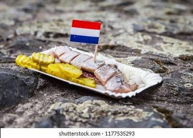 Amsterdam / The Netherlands - December 16 2018: traditional Dutch street food - herring with onions and pickles