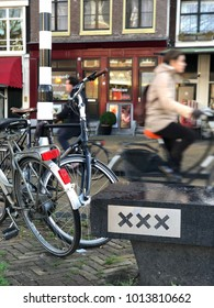 Amsterdam, Netherlands - December 17, 2017: Local commuters and tourists pass each other on bikes on the streets of Amsterdam.