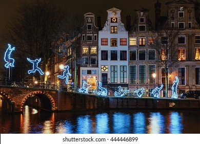 Amsterdam, Netherlands  December 18, 2015: Light Festival Amsterdam, a light figure makes a somersault with as decor Amsterdam Canal Houses and bridge