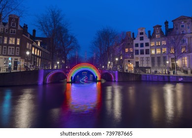 "Amsterdam, The Netherlands - December 24, 2016: Amsterdam canal Herengracht during the Amsterdam Light Festival and bridge with artwork ""Bridge of the Rainbow"" by Gilbert Moity."