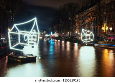 Amsterdam, The Netherlands, December 26, 2017:  Cottages of light float above the canal during the Festival of Light in Amsterdam