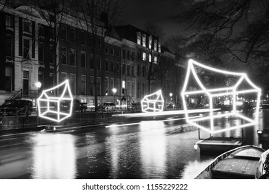 Amsterdam, The Netherlands, December 26, 2017:  Black and white picture of cottages of light float above the canal during the Festival of Light in Amsterdam