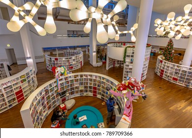 AMSTERDAM, NETHERLANDS - DECEMBER 29, 2016: Interior of a modern library with bent bookshelfs and funny lighting in the Netherlands