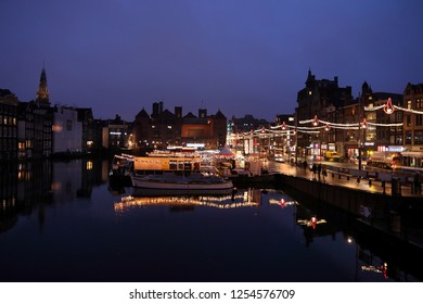 AMSTERDAM, NETHERLANDS - DECEMBER 6, 2018: Before dawn Damrak canal reflection with Christmas lights in Amsterdam, Netherlands. Amsterdam is the capital city of The Netherlands.