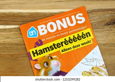 Amsterdam, the Netherlands - December 9, 2018: Grocery shop sale flyer or advertising brochure, of Dutch supermarket Albert Heijn against a wooden background.