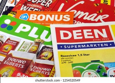 Amsterdam, the Netherlands - December 9, 2018: Stack of grocery shop sale flyers or advertising brochures, of Dutch supermarkets against a wooden background.