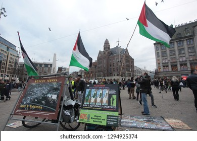Amsterdam, the Netherlands, Europe: January 6, 2019: horizontal photo of a group protest agains Israel, with signs and flags, outdoors on a cloudy day in Dem square in front of the Palace