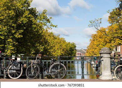 Amsterdam, The Netherlands, Europe traveling concept. Vibrant flowers and bicycles on a bridge near river canals famous UNESCO world heritage architecture.