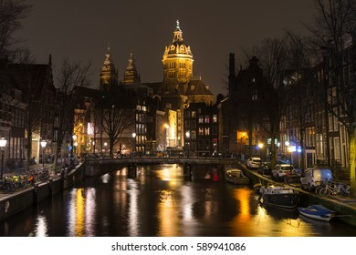 Amsterdam, Netherlands - February 09, 2017. Red Light District. View from a bridge in Voorburdwal canal on the basilica of St.Nicholas in the evening time. The buildings are illuminated very nice.