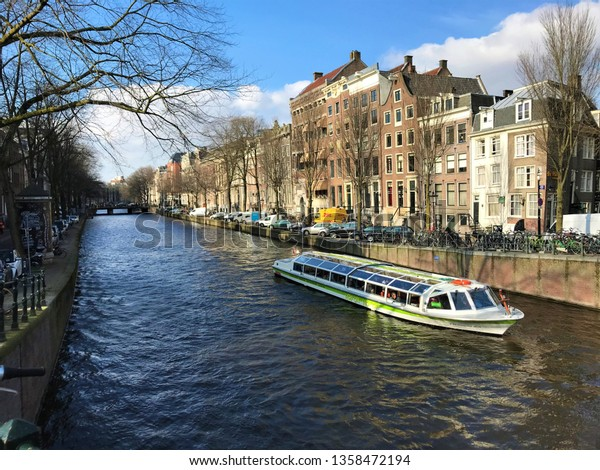 Amsterdam, Amsterdam / Netherlands - February 12 2018: canal boat and street view daytime