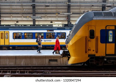 AMSTERDAM, THE NETHERLANDS - February 18, 2019: Amsterdam centraal train station with people traveling by train and sprinter, NS Intercity train at the main station.