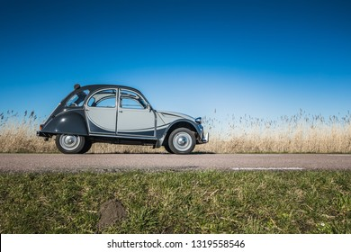 AMSTERDAM, NETHERLANDS - FEBRUARY 20, 2018: A French oldtimer classic car vehicle and industrial design icon, the Citroen 2CV Charleston or Citroën 2CV on a country road in summer with a blue sky