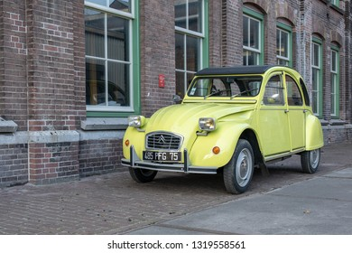 AMSTERDAM, NETHERLANDS - FEBRUARY 20, 2018: A French oldtimer classic car vehicle and industrial design icon, the Citroen 2CV or Citroën 2CV in the color lemon yellow, called Jaune Cedrat in warehouse