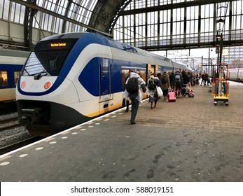 Amsterdam, Netherlands - February 23, 2017: Ordinary passengers near electric sprinter train on Amsterdam Central Station in rainy day