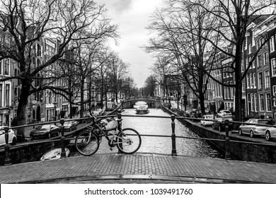 Amsterdam, The Netherlands - February 26, 2010: Bicycle on the street near water canal. Bike is very popular transport in Amsterdam