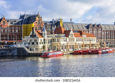 AMSTERDAM, NETHERLANDS - FEBRUARY 27, 2018: View of embankment on Open Havenfront with Train Station on background. Open Havenfront is water between Prins Hendrikkade and Station Island in Amsterdam.
