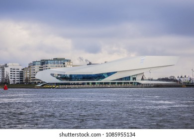 AMSTERDAM, NETHERLANDS - FEBRUARY 27, 2018: Wonderful view of river IJ Embankment with modern building. IJ River divides the north and south of Amsterdam.
