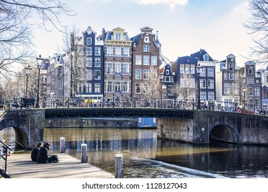 AMSTERDAM, NETHERLANDS - FEBRUARY 27, 2018: Beautiful view of Amsterdam canals, bridge and typical Dutch houses. Amsterdam has more than one hundred kilometers of canals, 90 islands and 1,500 bridges.