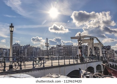 AMSTERDAM, NETHERLANDS - FEBRUARY 27, 2018: Beautiful view of famous Skinny bridge (Magere Brug, 1691). Skinny bridge - traditional double leaf Dutch Bascule Bridge connecting sides of river Amstel.
