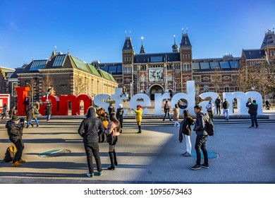 """AMSTERDAM, NETHERLANDS - FEBRUARY 28, 2018: Tourists at the famous sign """"I amsterdam"""" at Museum Square near Rijksmuseum in Amsterdam."""