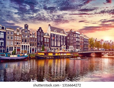 Amsterdam, Netherlands. Floating Houses and houseboats and boats at channels by banks. Traditional dutch dancing houses among trees. Evening autumn street above water pink sunset sky with clouds.