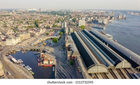 Amsterdam, Netherlands. Flying over the city rooftops.  Amsterdam Central Station ( Amsterdam Centraal ), Aerial View