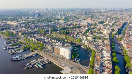 Amsterdam, Netherlands. Flying over the city rooftops towards Amsterdam Central Station ( Amsterdam Central ), Aerial View