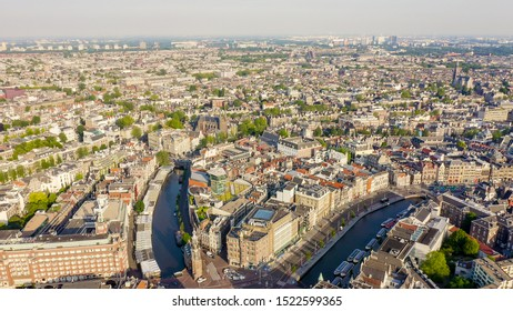 Amsterdam, Netherlands. Flying over the city rooftops. The historical part of the city with urban shipping channels, Aerial View