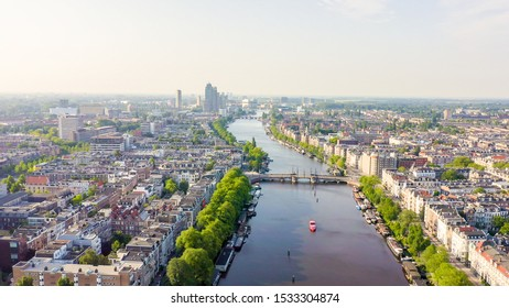 Amsterdam, Netherlands. Flying over the city rooftops. Amstel River, Aerial View