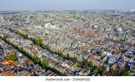 Amsterdam, Netherlands. Flying over the city rooftops towards Amsterdam Central Station ( Amsterdam Centraal ) and around the Oudekerk church ( De Oude Kerk ), Aerial View