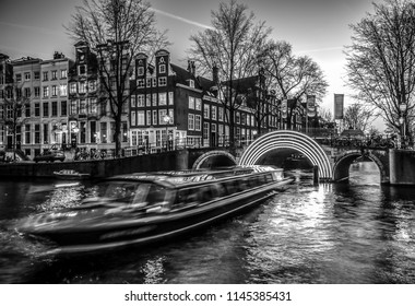 AMSTERDAM, NETHERLANDS - JANUARY 10, 2017: Cruise boats rush in night canals. Light installations on night canals of Amsterdam within Light Festival. January 10, 2017 in Amsterdam - Netherland.