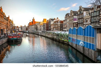AMSTERDAM, NETHERLANDS - JANUARY 10, 2017: Famous vintage buildings & canals of Amsterdam city at sun set. General landscape view. January 10, 2017 - Amsterdam - Netherlands.