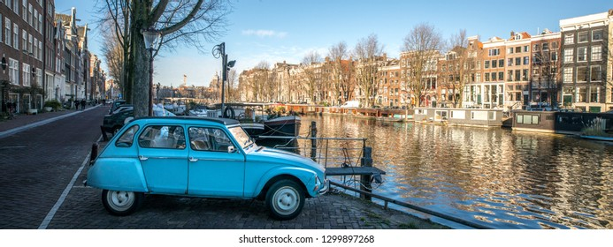 AMSTERDAM, NETHERLANDS - JANUARY 10, 2019: A sky blue Citroën Dyane, the sister of a Citroen 2CV, is parked alongside the beautiful Unesco protected canals of Amsterdam, the capital of The Netherlands