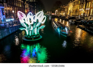 AMSTERDAM, NETHERLANDS - JANUARY 11, 2017: Cruise boats rush in night canals. Light installations on night canals of Amsterdam within Light Festival. January 11, 2017 in Amsterdam - Netherland.